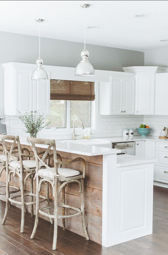 a white farmhouse kitchen with a kitchen island that features a raised countertop for eating here