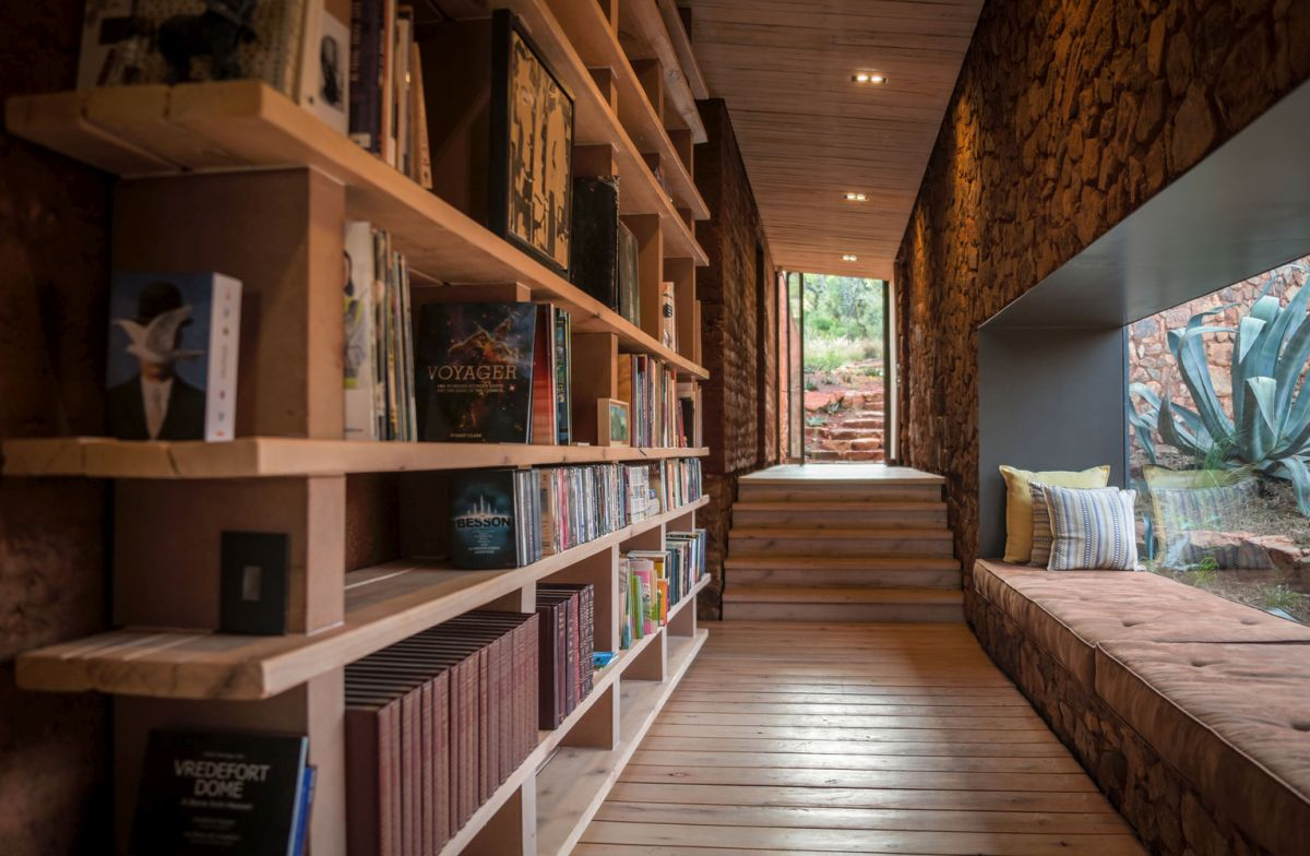 A corridor is used to create a reading space   one wlal is taken by a large bookshelf and there's a windowsill reading space in here