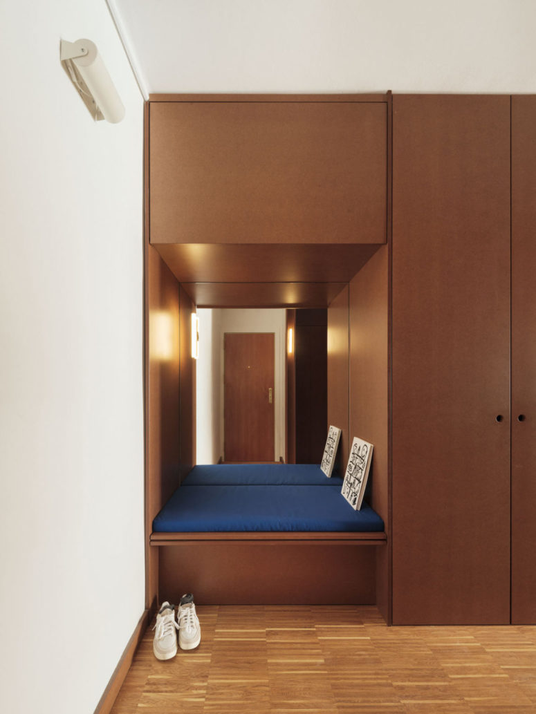 The entryway features a lot of storage space and a built-in seat with a mirror