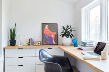 The work space is done with a large corner desk, white cabinets, bold artworks and potted plants