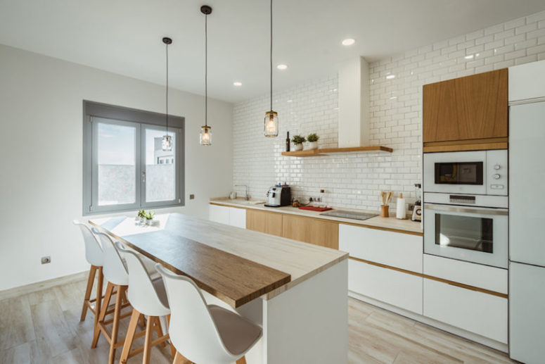There's another, cozy little kitchen done in white and natural light-colored wood, with subway tiles and pendant lamps