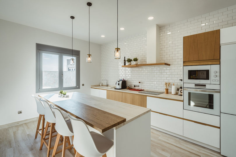 There's another, cozy little kitchen done in white and natural light colored wood, with subway tiles and pendant lamps