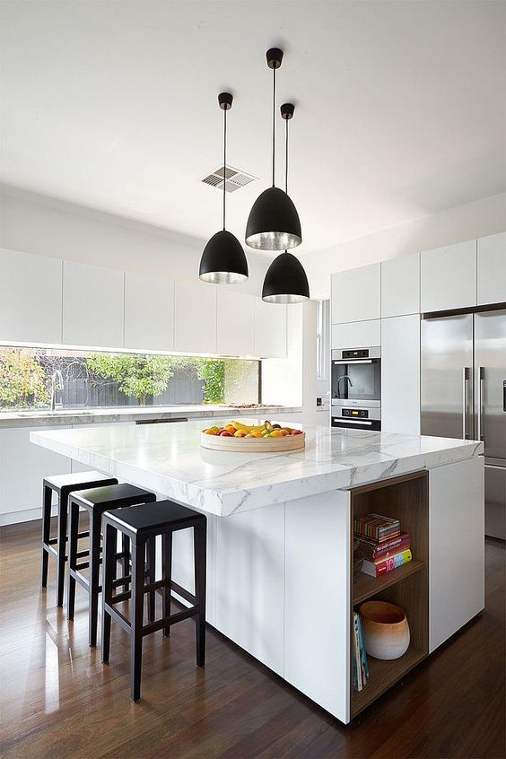 a contemporary kitchen done in white, with an oversized kitchen island that features storage and a countertop for eating at the same time