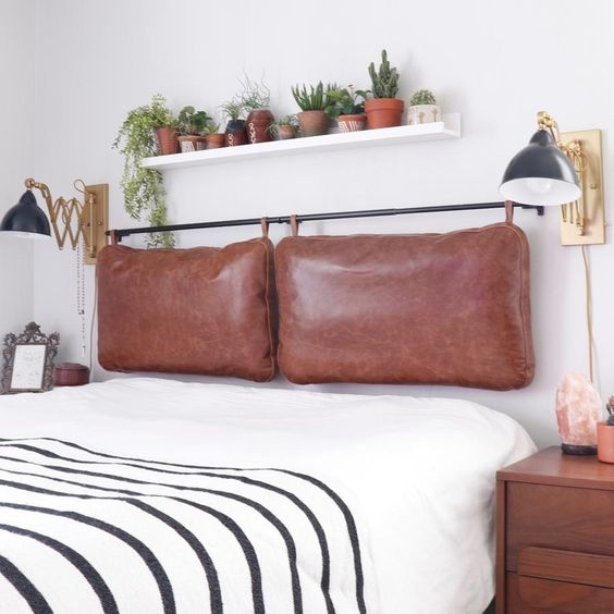 a contemporary meets boho bedroom with a brown leather pillow headboard on a black holder