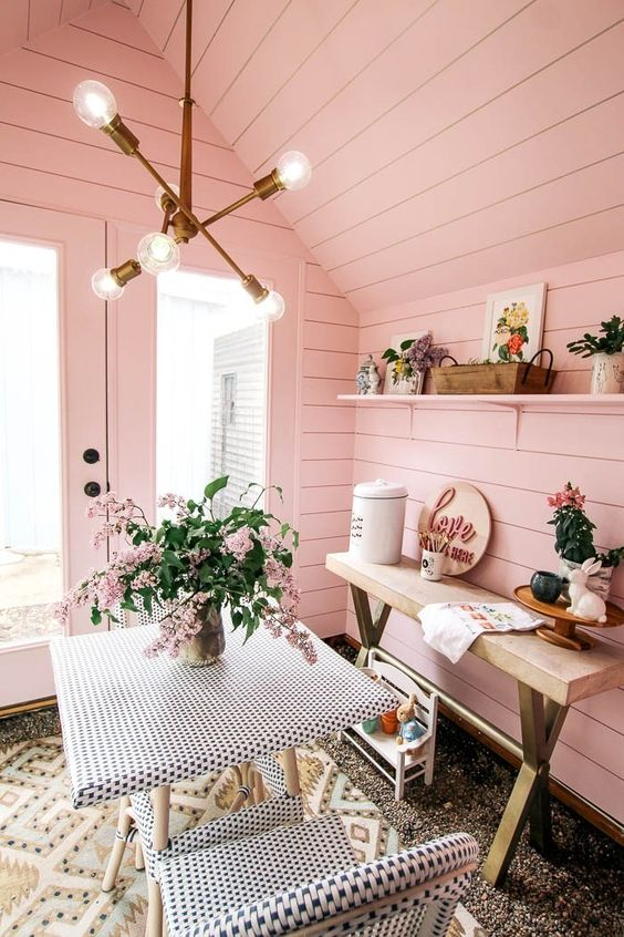 a cozy and cute she shed with a small dining space, a console table and some toys for kids to spend time here