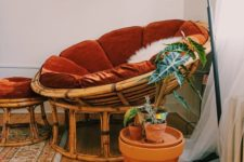 10 a rattan papasan chair with a rust velvet futon and a matching footrest plus some potted plants