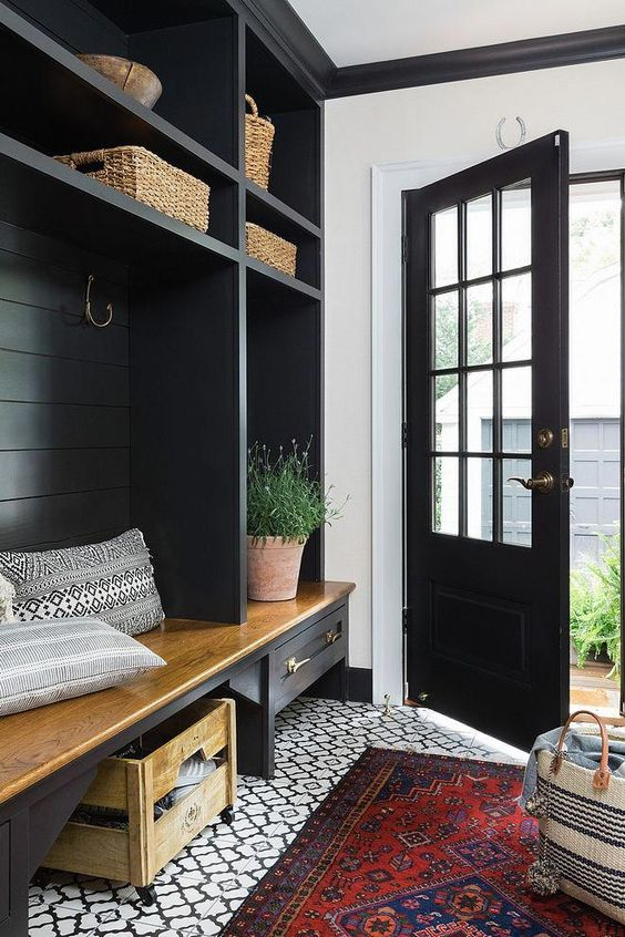 a small farmhouse entryway with onyx-colored furniture and a door that contrast white and red touches all over