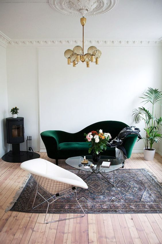 a vintage dark green velvet sofa and a medallion on the ceiling to add a chic look to the space