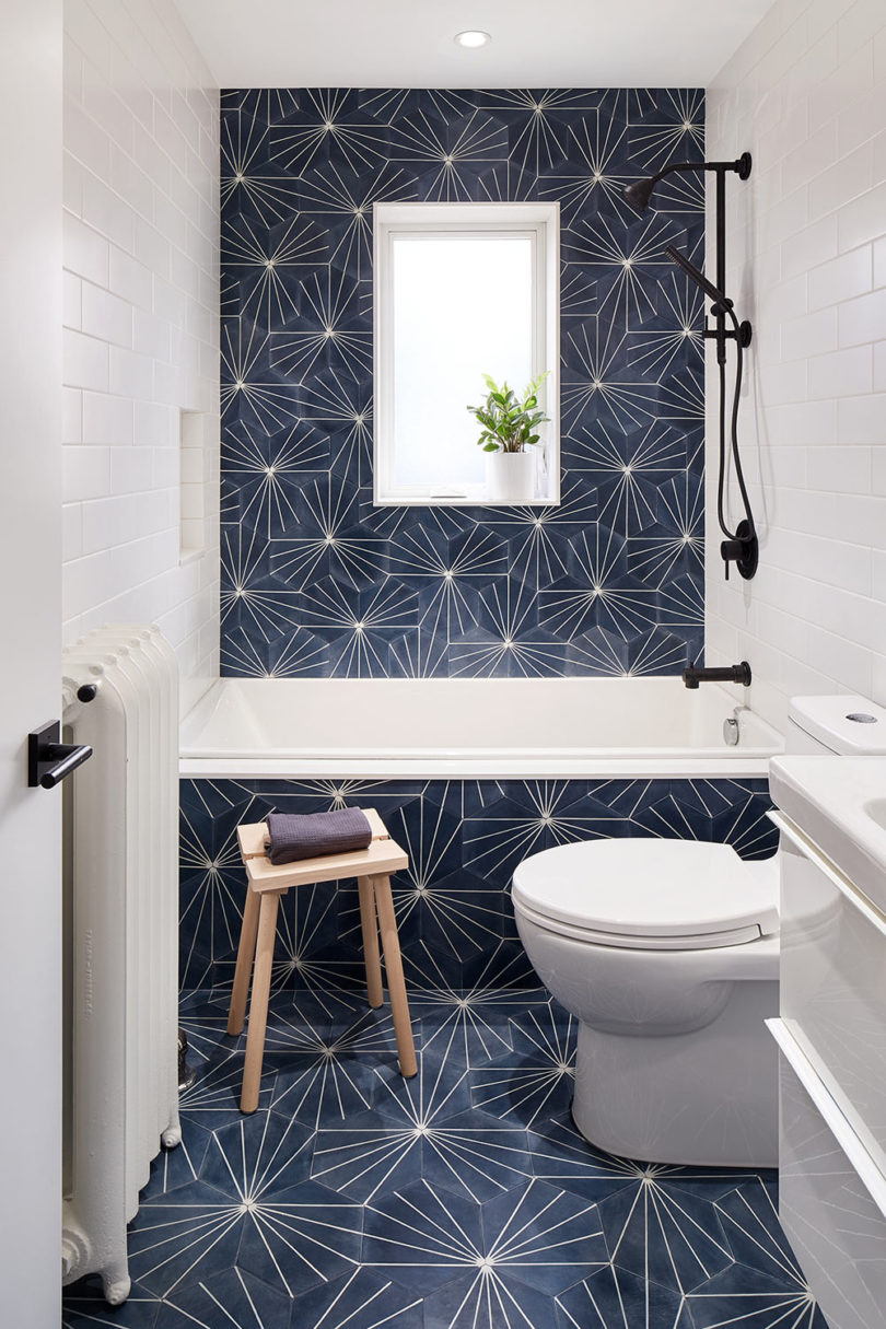 The bathroom is clad with printed navy tiles paired with white subway ones, there's a window for light