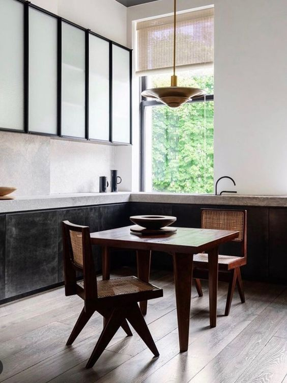 The dining space is located in the kitchen, it's done with wicker chairs and a cool metal pendant lamp