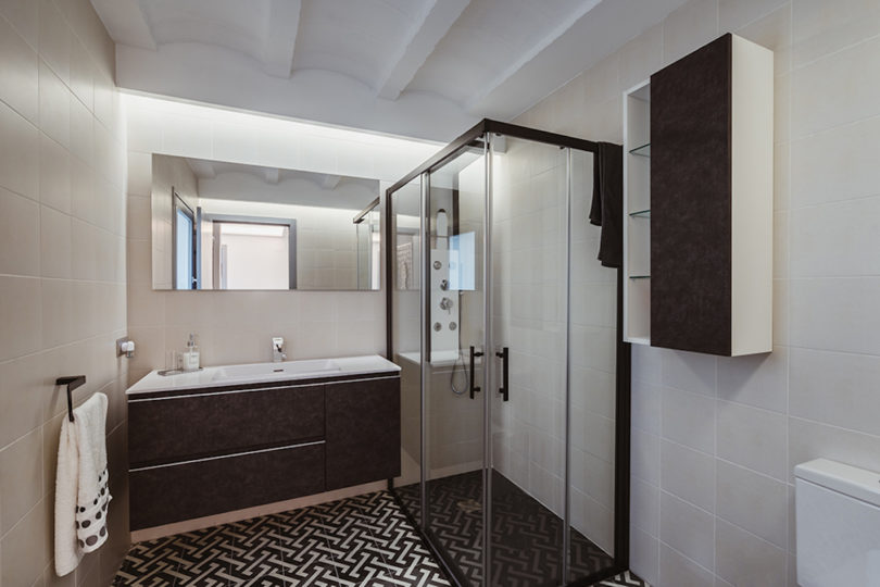 The second bathroom is done in black and white, with printed tiles and a shower space