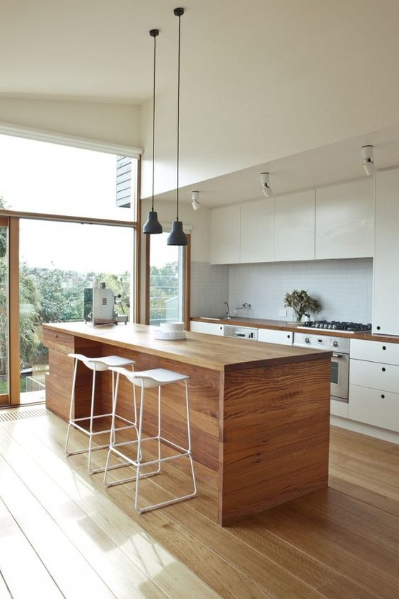 a modern kitchen in white, with a wooden kitchen island that is good both for eating and cooking here