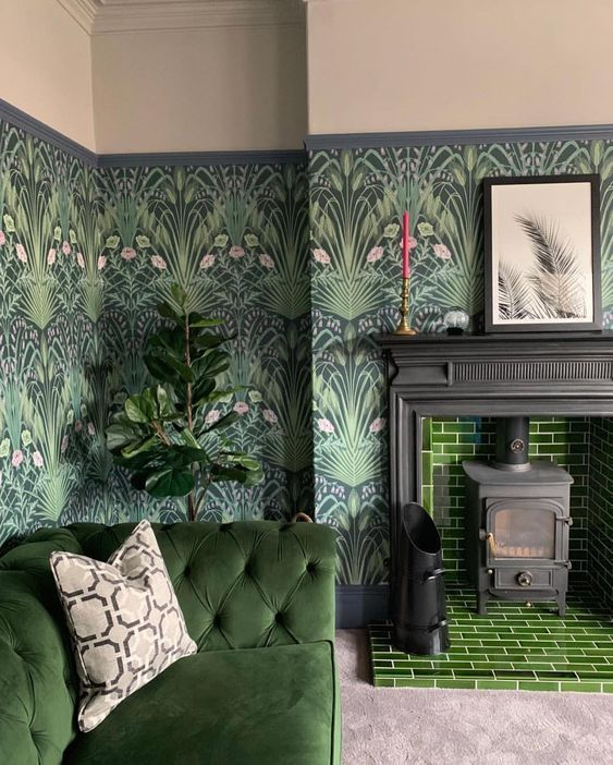 a moody living room with dark botanical wallpaper, green tiles, a matching sofa and potted plants feels outdoors