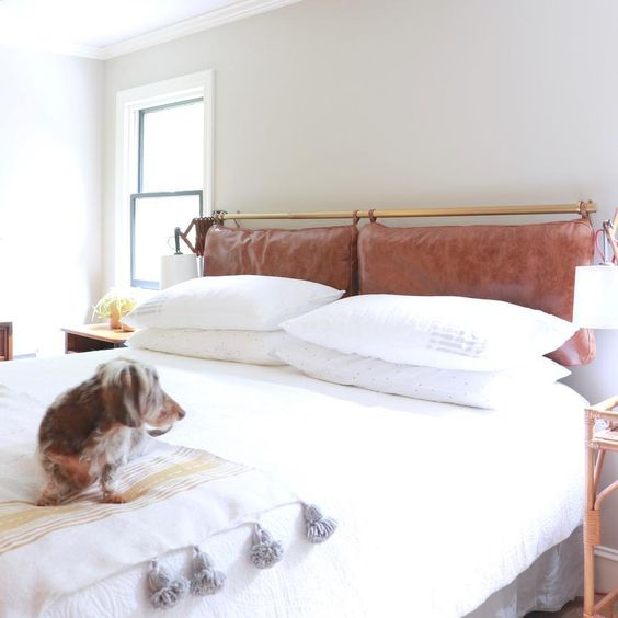 a neutral and serene space done with a brown leather pillow headboard on a brass holder that adds color and texture