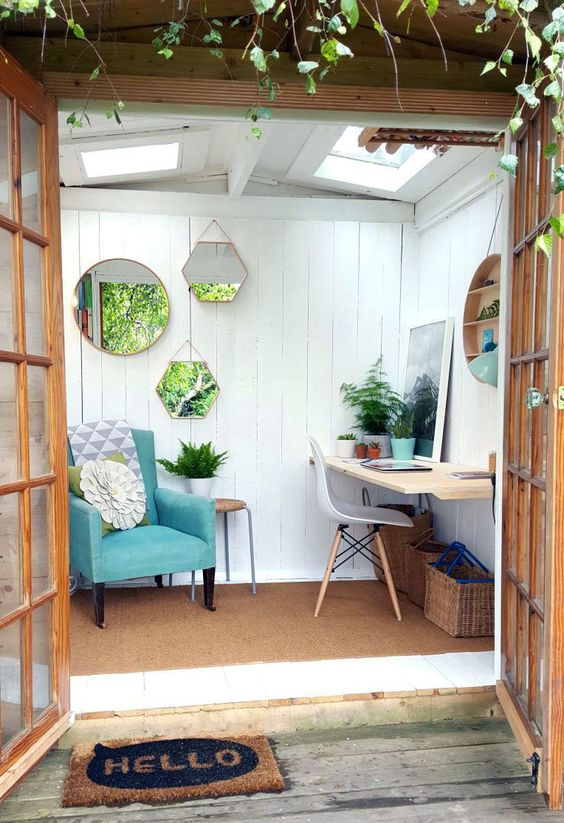 a small garden shed with a reading nook and a small workspace plus an arrangement of mirrors to enlarger the space