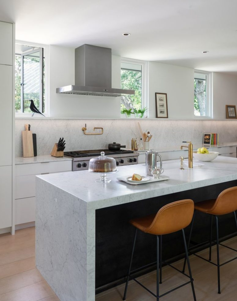 The kitchen is neutral and very airy, with stone countertops, leather stools and touches of gold here and there