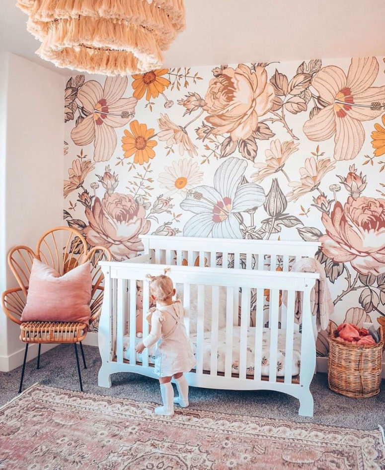 a colorful girl's nursery in peachy and coral with a statement large scale floral print wall that creates a mood here