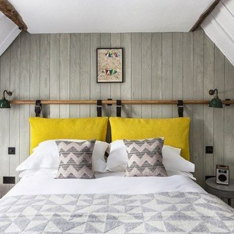 a neutral bedroom with a plenty of pattern and a bright yellow pillow headboard hanging on leather belts looks bright