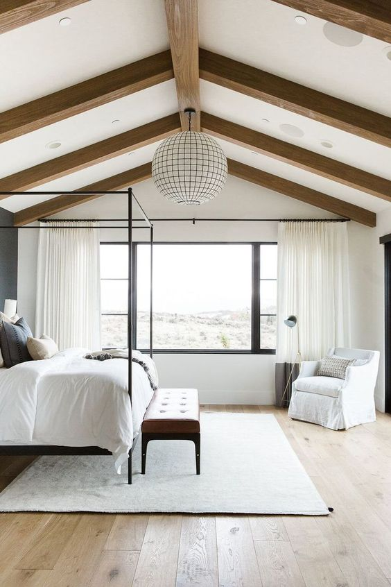 a neutral farmhouse bedroom with wooden beams on the ceiling and a statement sphere lamp