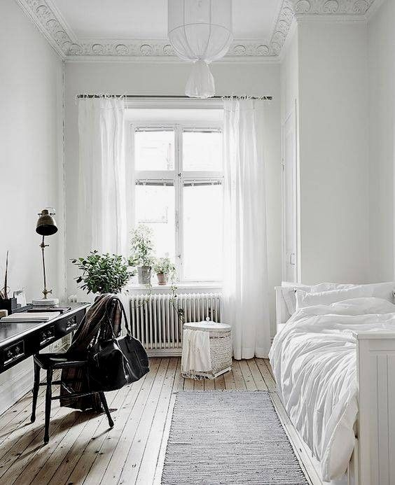 a serene and airy guest bedroom with lots of white and a vintage black desk plus chair to stand out