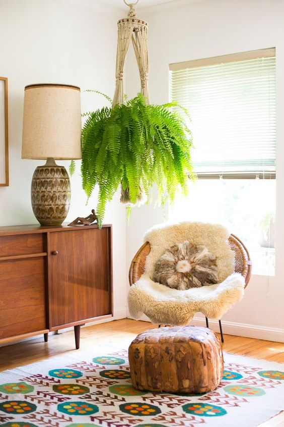a woven papasan chair with a faux fur rug and a pillow paired with a faux leather ottoman for a boho space