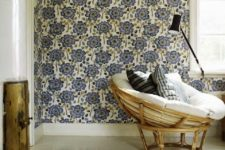 13 a chic reading nook with a blue wallpaper wall, a rattan papasan chair and graphic pillows