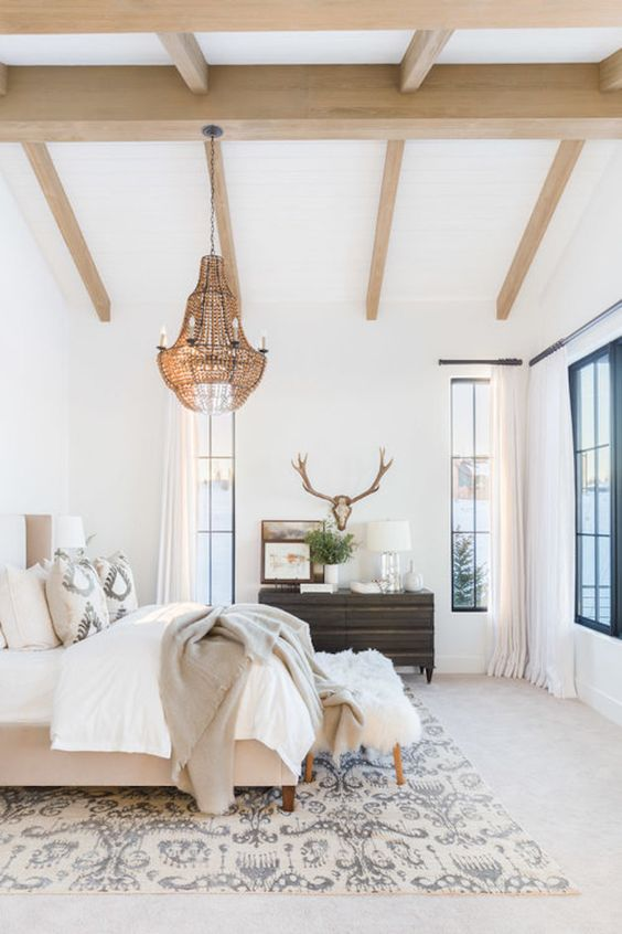 a neutral eclectic bedroom with wooden beams on the ceiling, a statement brass chandelier with candles