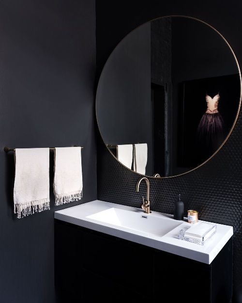 an onyx powder room with a contrasting white sink, white towels and shiny black penny tiles