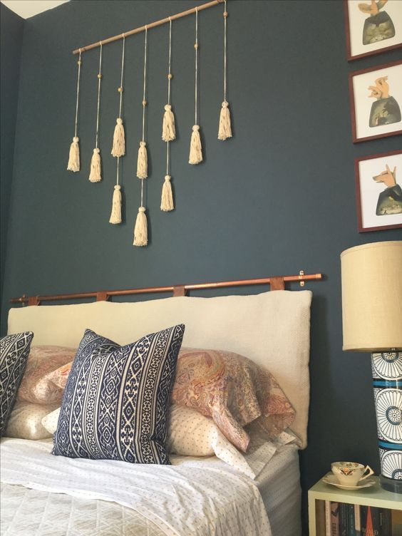 a boho bedroom with a black statement wall, a tassel hanging, a neutral cushion headboard on a copper holder