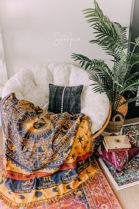a boho reading nook with a rattan papasan chair with a white futon and a bright zodiac blanket plus a plant and colorful rugs