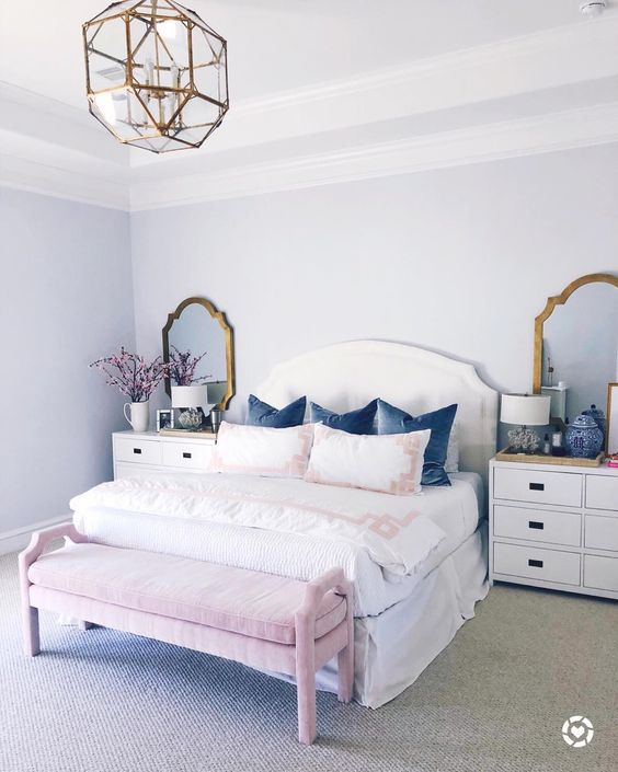 a girlish bedroom with brass framed mirrors and a matching geometric chandelier for a shiny touch