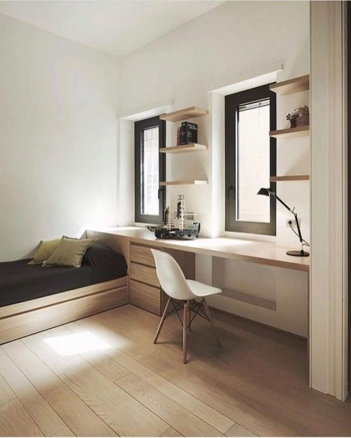 a minimalist guest bedroom with a bed and a desk by the window is done flawless and seamless