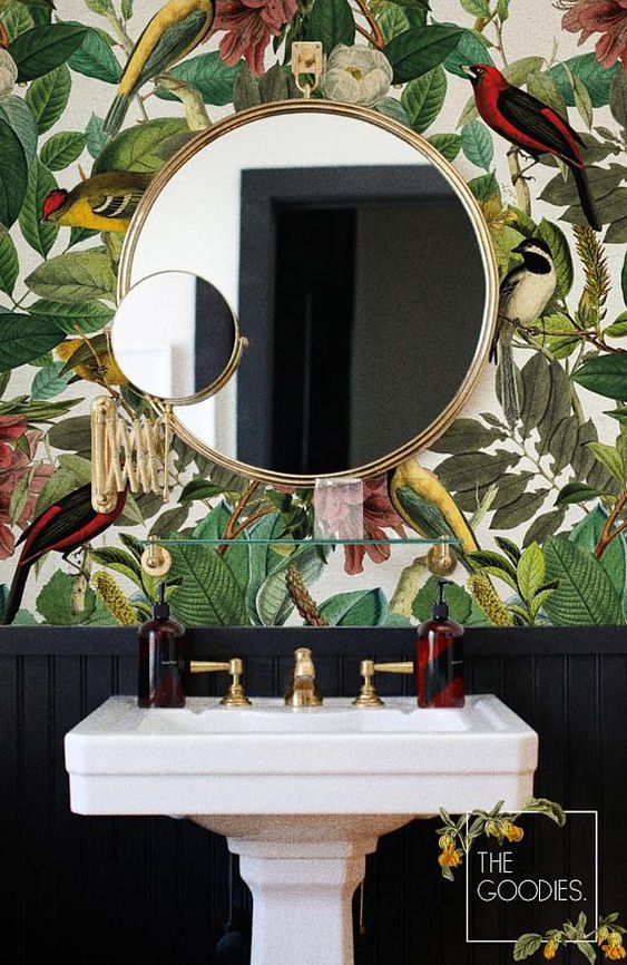 a moody powder room with bright flora and fauna wallpaper and some gilded touches for a bold look