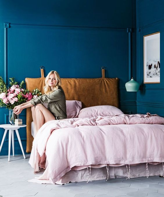 a bright bedroom with bold blue walls, a mint pendant lamp and a bed with a hanging leather headboard