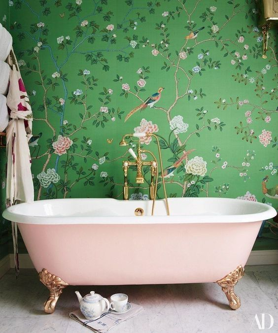 a chic girlish bathroom with flora and fauna wallpaper, a pink clawfoot tub and gold fixtures looks amazing