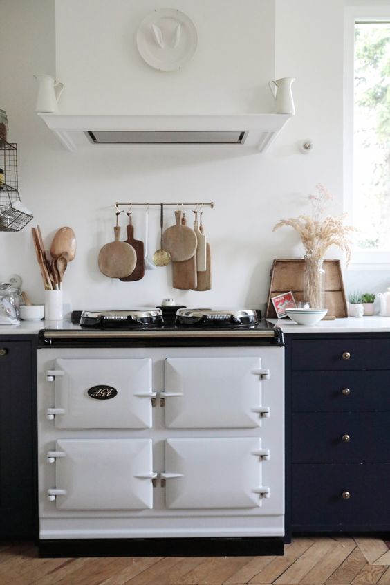 a contemporary kitchen finished off with a white vintage cooker and a matching hood for a bolder look