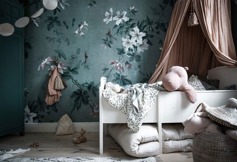 a refined nursery with a green floral accent wall and touches of dark green and soft blush and pink for a chic look