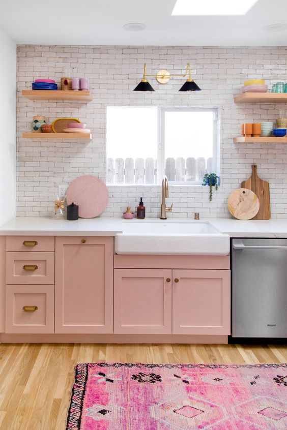 a small kitchen done with pink cabinets, a bright printed rug and neutrals to create a contrast