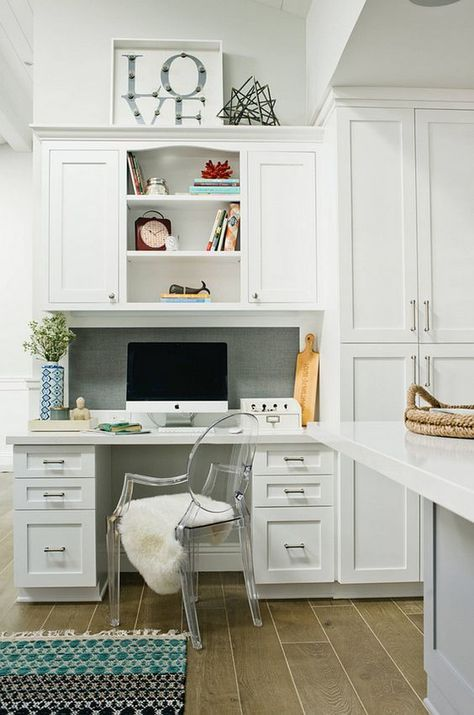 a white farmhouse kitchen with a tiny yet very functional home office nook integrated into decor
