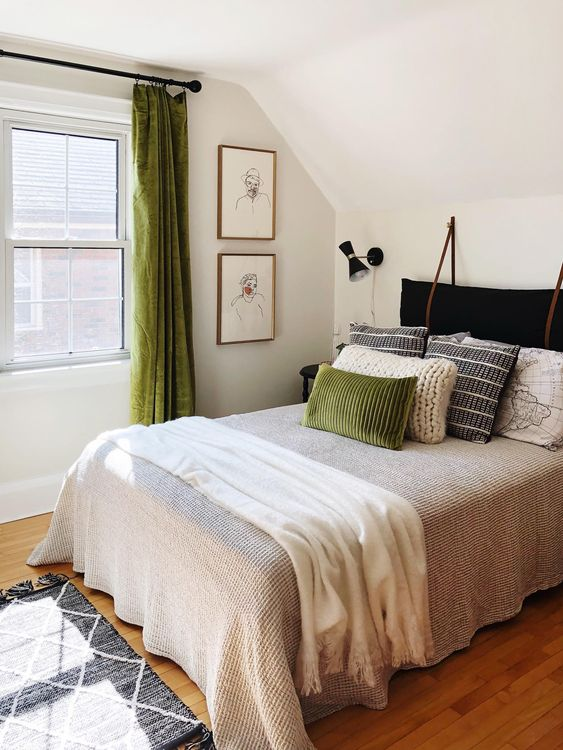 a cozy bedroom with green linens, printed and knit pillows and a black velvet cushion headboard