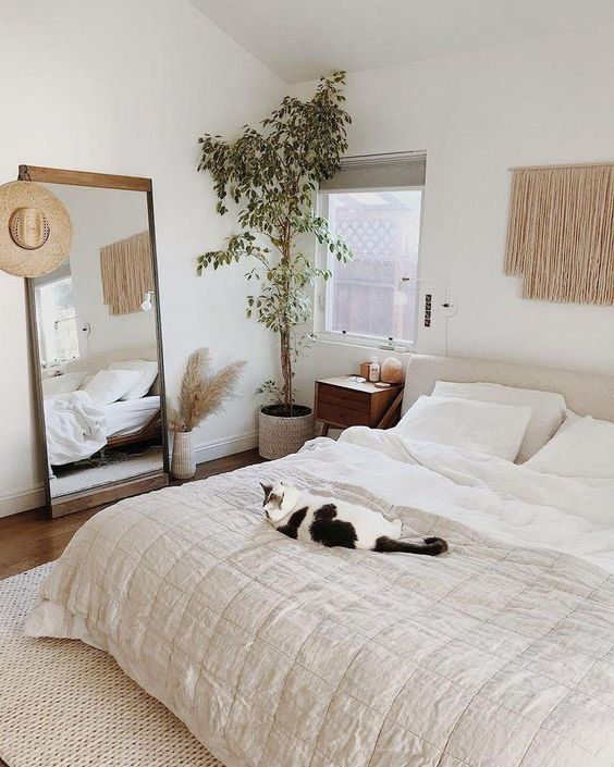 a neutral boho bedrom with a statement potted plant in the corner that makes it fresher and more welcoming