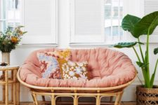 17 a rattan mamasan chair with a pink futon, floral pillows and blooms and potted plants for a boho space