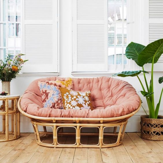 a rattan mamasan chair with a pink futon, floral pillows and blooms and potted plants for a boho space