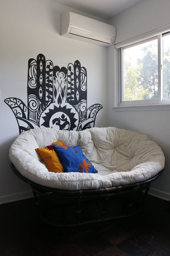 a cool papsan chair with cute pillows