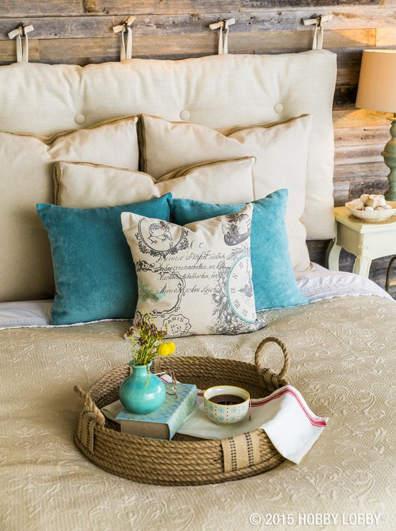 a cozy rustic bedroom with a neutral hanging cushion headboard with tufting for a bold touch