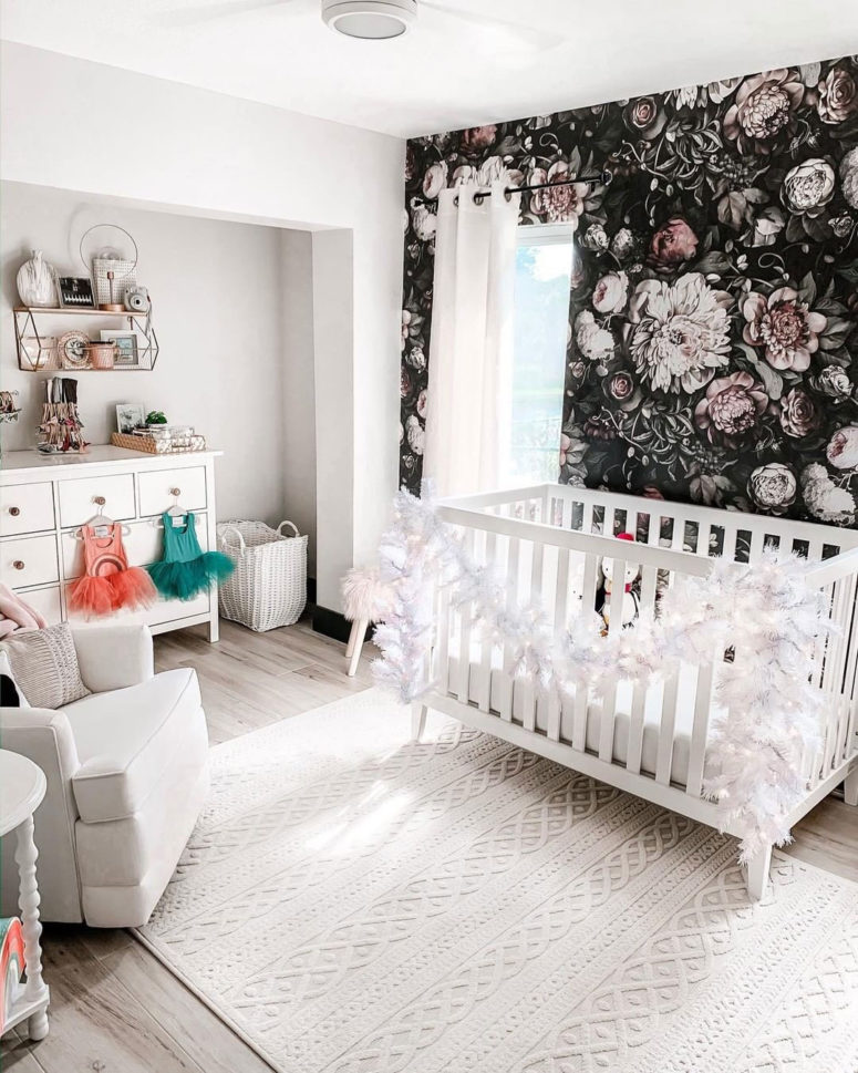 a gorgeous kid's nursery with a refined black realistic floral print wall that stands out in a white space