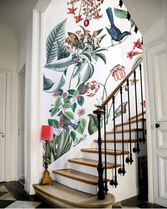 a refined entryway with a classic staircase and fantastic bright floral and faune wallpaper plus a little floor lamp in red