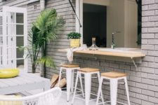 18 an outdoor-indoor bar with stools, a countertop and a dining space by its side plus some potted greenery