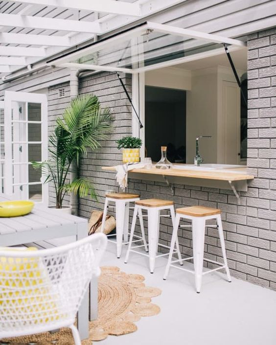 an outdoor indoor bar with stools, a countertop and a dining space by its side plus some potted greenery