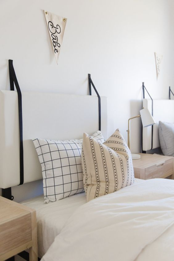a double guest bedorom with white cushion headboards hanging on black cords looks serene and fresh